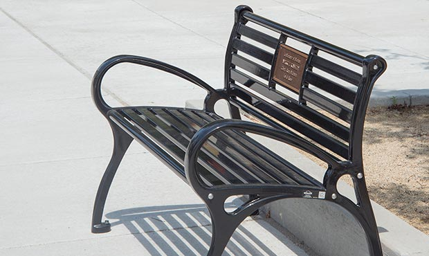 Schenley bench with a plaque on the sidewalk