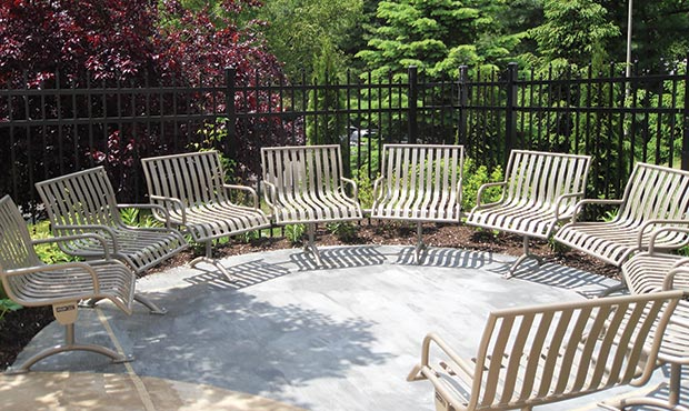 Custom Pullenium modular curved bench with arms in garden setting