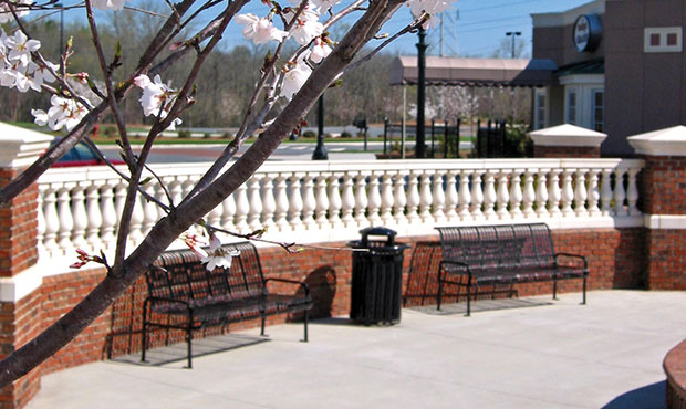 Midtown Benches and a matching receptacle with blossoms in the foreground