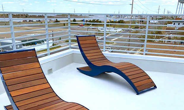 A pair of Loma Chaise Lounges on a rooftop viewing deck