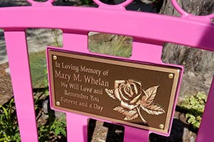 Memorial cast bronze plaque on the back of a Sienna Bench with personal messages attached