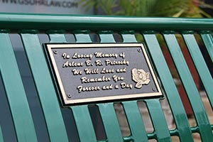 Bronze plaque with text and rose image on bench back