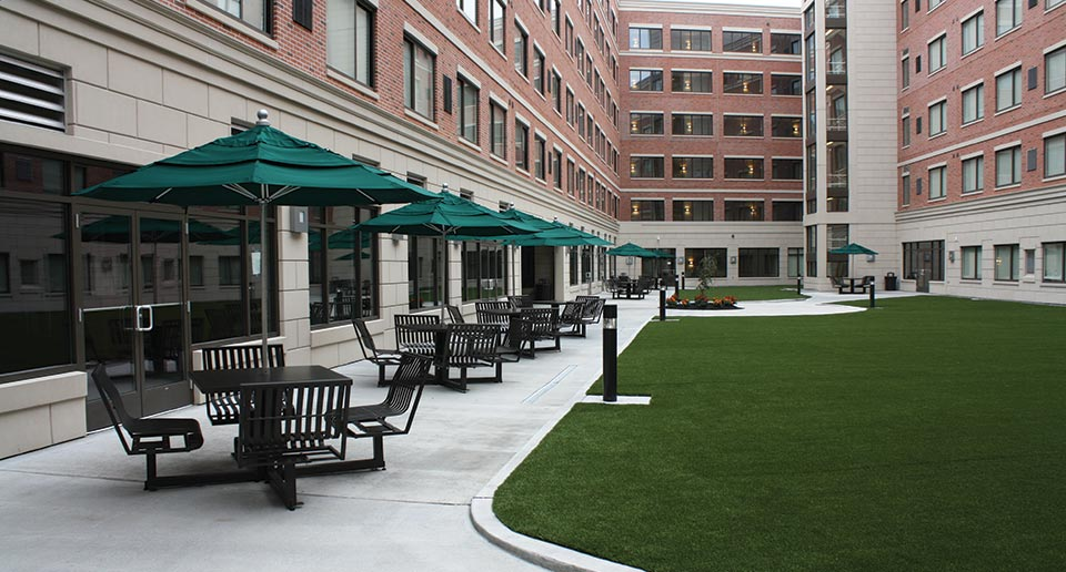 Hapsburg Table Sets with Umbrellas fill a courtyard with covered seating space
