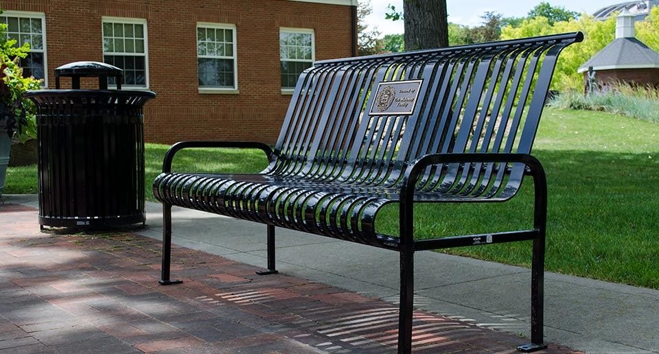 Midtown Bench with Back and inset Plaque and Litter Receptacle on a college campus