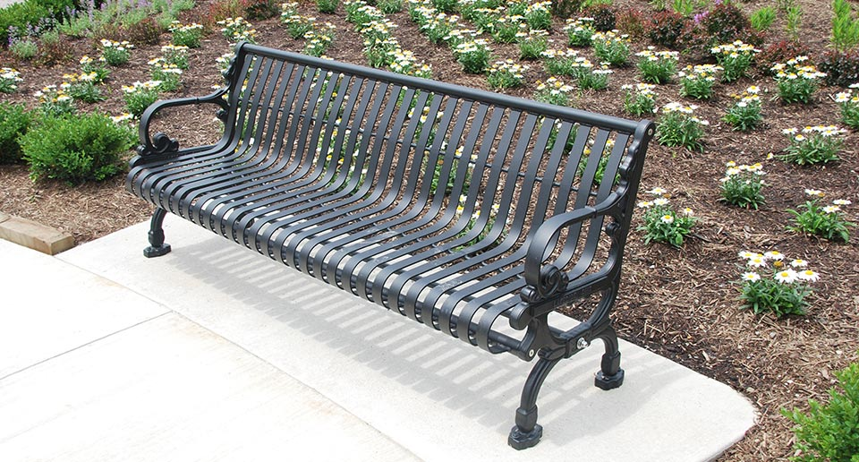 Lamplighter Bench with Back set amidst a landscaped garden environment