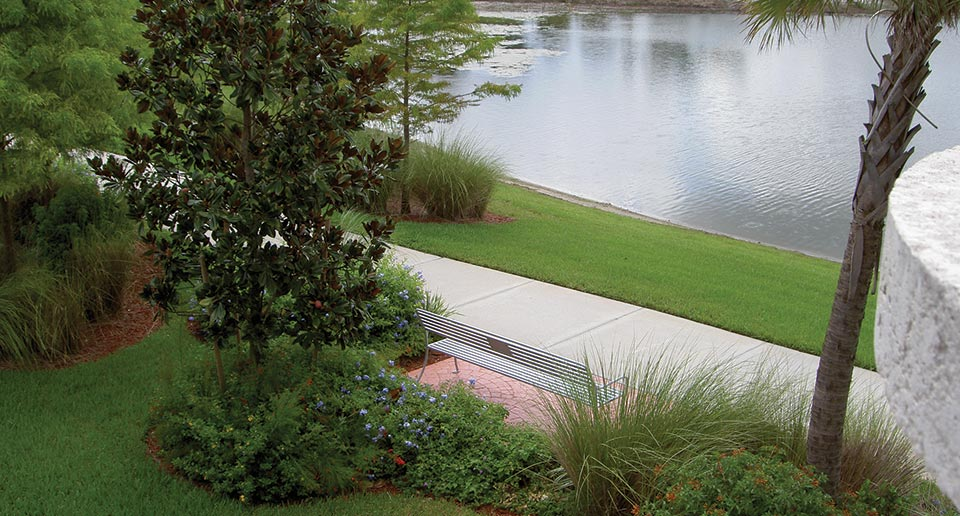 Sienna Bench with Back and Plaque by a scenic pond