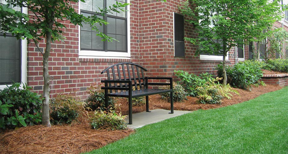 McConnell Bench with Back situated among landscaped flora