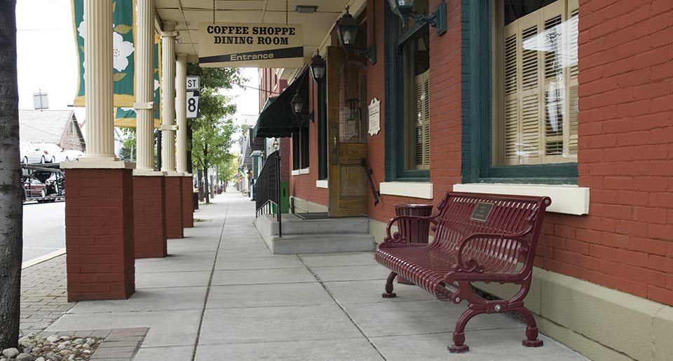 Lamplighter Bench with Back with Plaque in a main street setting