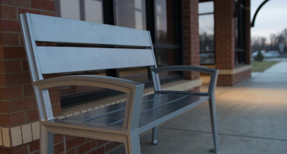 Everett Bench with Back situated at a public bus shelter